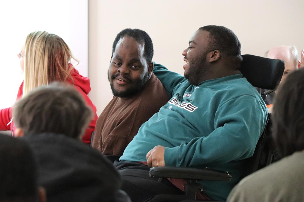 man in a wheelchair with his arm around another man laughing