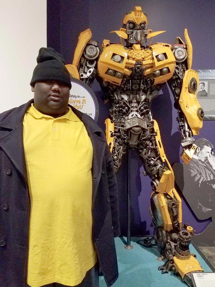 man wearing a hat standing next to a robot