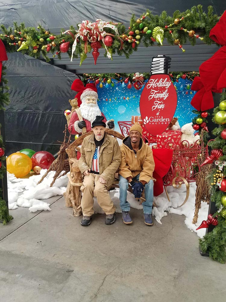 two men sitting on a bench at the Garden Factory during the holidays