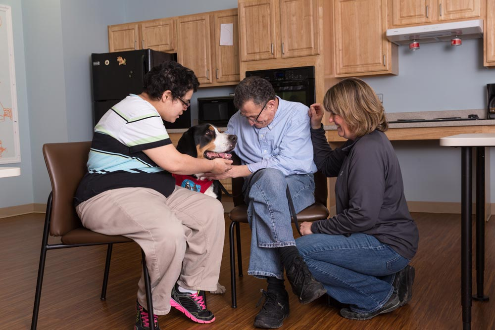 three people petting a dog in a home