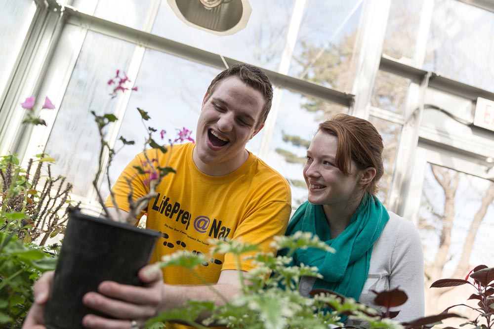 man and woman in a greenhouse looking at plants
