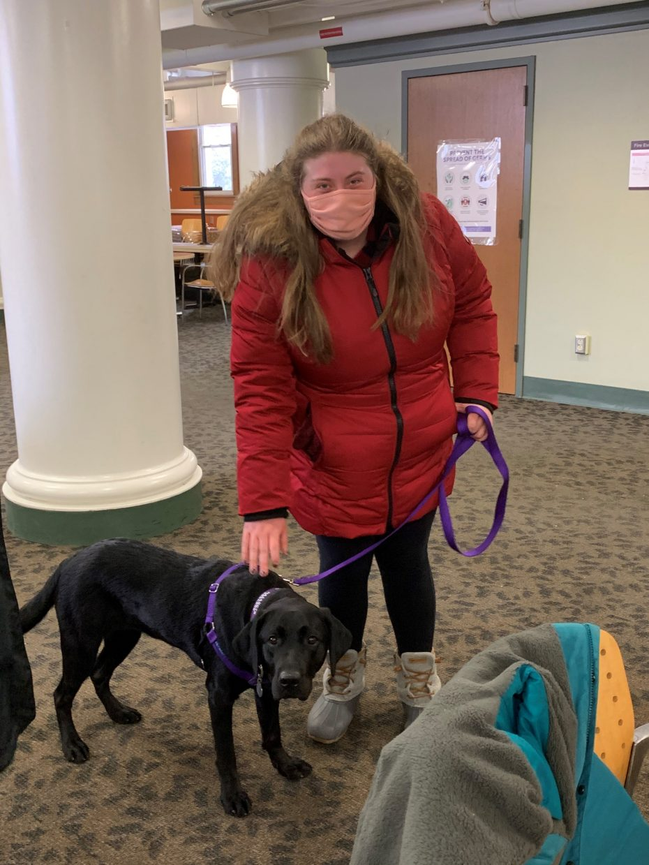 girl standing with black lab therapy dog in room